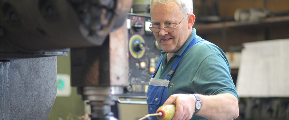 Älterer Mitarbeiter bedient eine Maschine