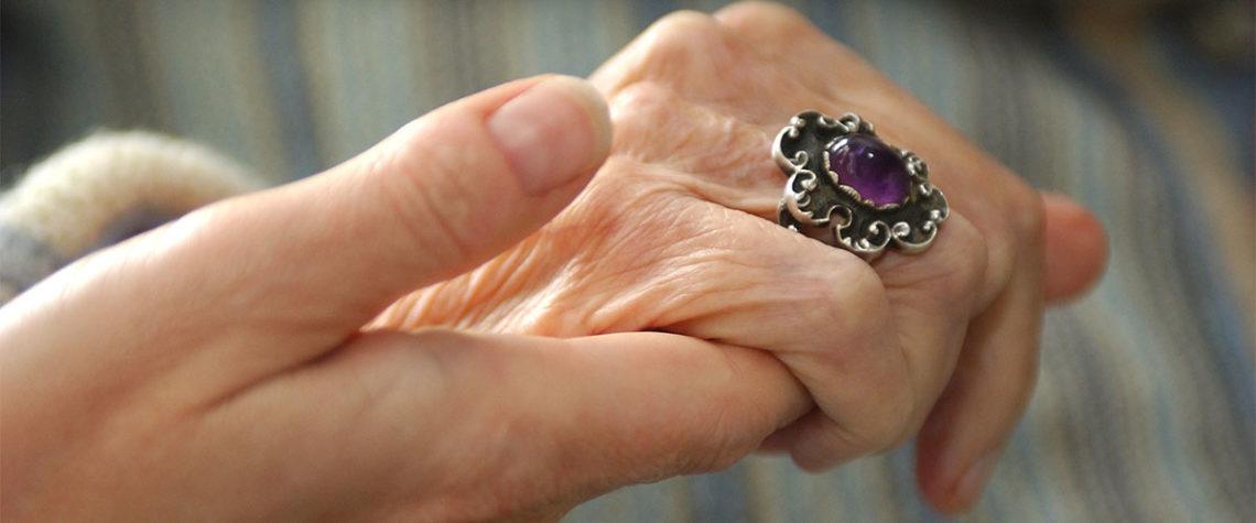 Ein jüngerer Mensch hält die Hand eines älteren Menschen